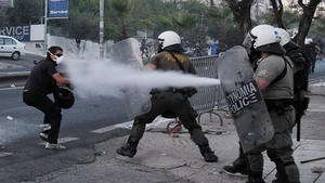 Police spray a protester with tear gas during clashes with anti-fascist demonstrators in the western Athens suburb of Keratsini