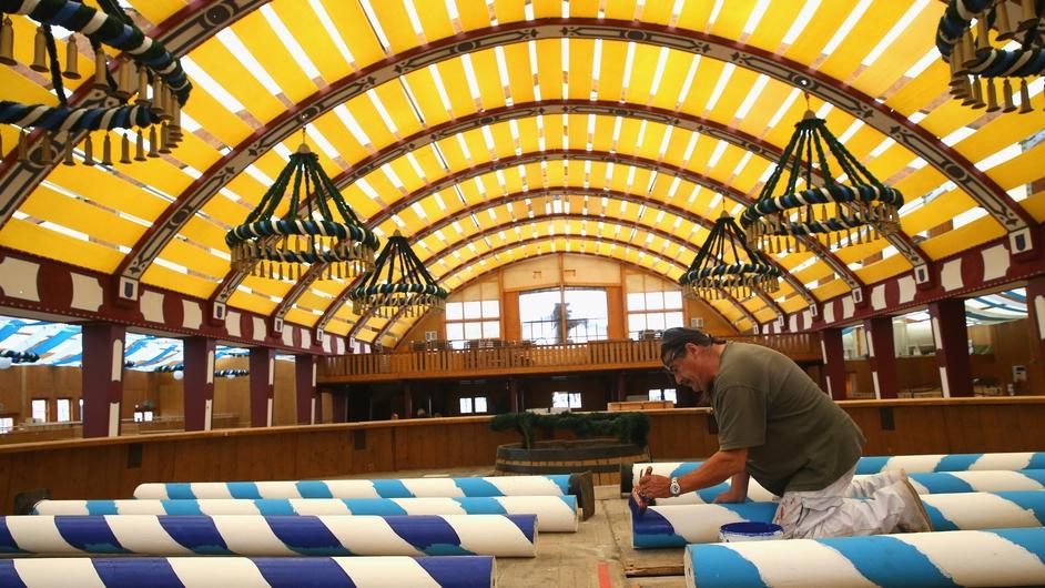 A worker painting Maibaum poles at the Loewenbraeu Festzelt three weeks ahead of Oktoberfest