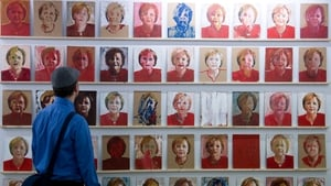 A visitor looks at German artist Peter Wilde's '60 Merkels' at the Berliner Liste fair for contemporary art in Berlin