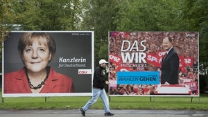 A man walks past a placard advertising CDU candidate German Chancellor Angela Merkel and SPD chancellor candidate Peer Steinbrueck in Berlin
