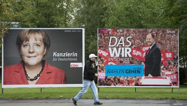 A man walks past a placard advertising CDU candidate German Chancellor Angela Merkel and SPD chancellor candidate Peer Steinbrueck in Berlin