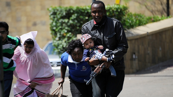 A Kenyan policeman carries a baby when helping some people to escape