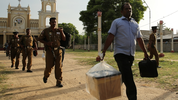 A Sri Lankan poll officer carries a sealed ballot box at a counting centre in Jaffna