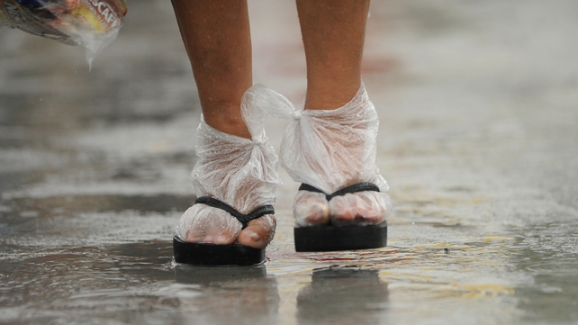 A woman uses plastic bags as socks to keep her feet from getting wet as she walks