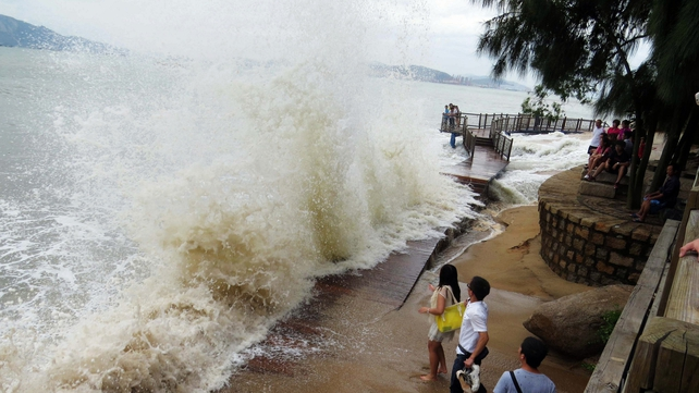 A group of Chinese visitors next to strong waves hitting the coast of Xiamen in southeast China's Fujian province