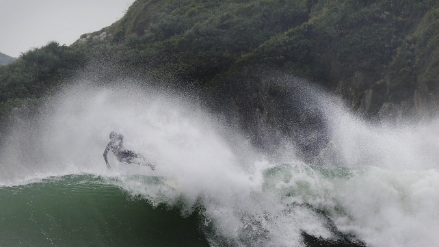 A surfer jumps from his board while catching an unusually large wave at Big Wave Bay in Hong Kong