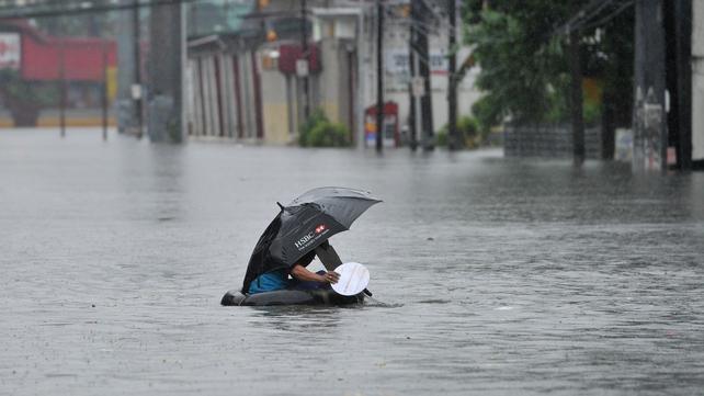 A resident using an innertube as a makeshift raft paddles through chest-deep floodwaters along a street in Manila