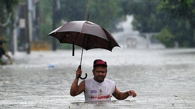 A man walks through deep floodwater in Manila, Philippines, where the typhoon has brought heavy rains