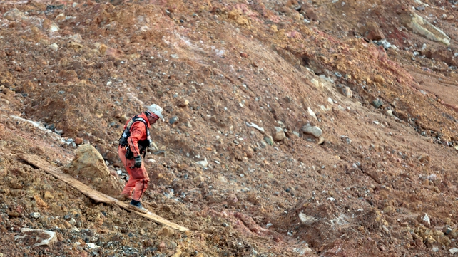 A member of the Mexican rescue team 'Topos' (Moles) searches for victims of a landslide