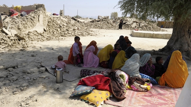 Villagers take shade under a tree after their houses were destroyed