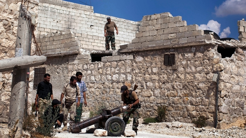 Rebel fighters load a shell into a cannon aimed at pro-regime forces in the Sheik Said neighbourhood of Syria's northern city of Aleppo