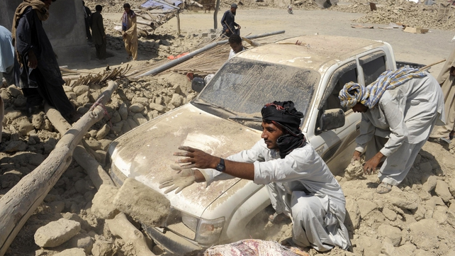 Men try to dig out a car from the rubble of destroyed buildings