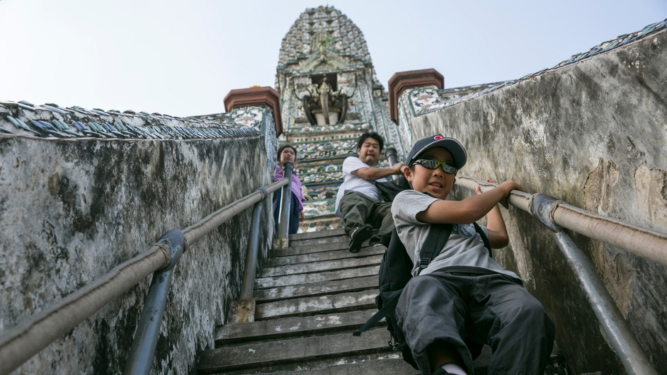 Tourists climb down the steep staircase of the temple of Wat Arun in Bangkok, Thailand