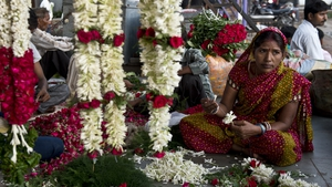 An Indian vendor prepares a floral garland at a wholesale flower market in New Delhi