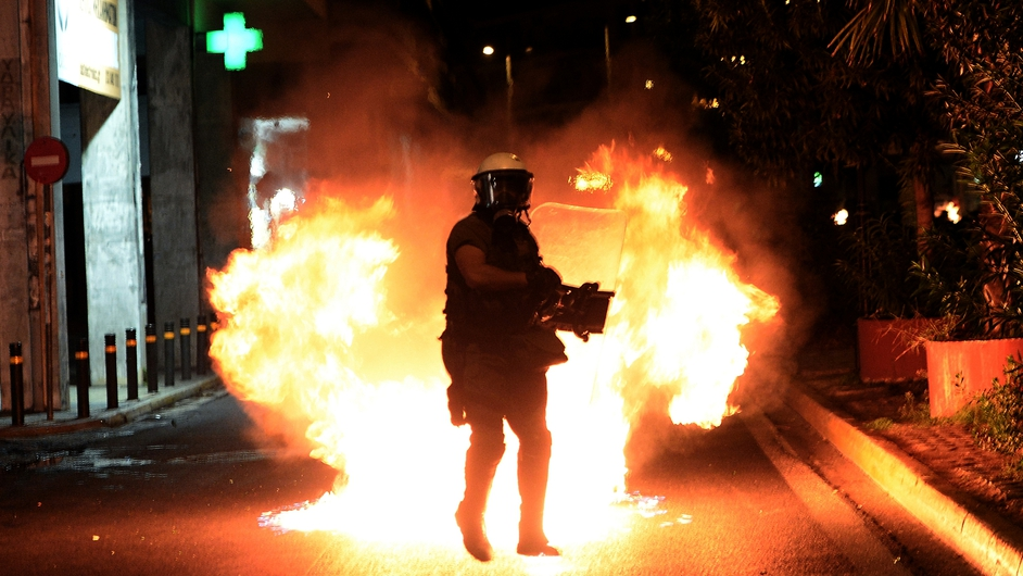 A petrol bomb explodes in front of riot police during clashes with demonstrators in Athens, Greece