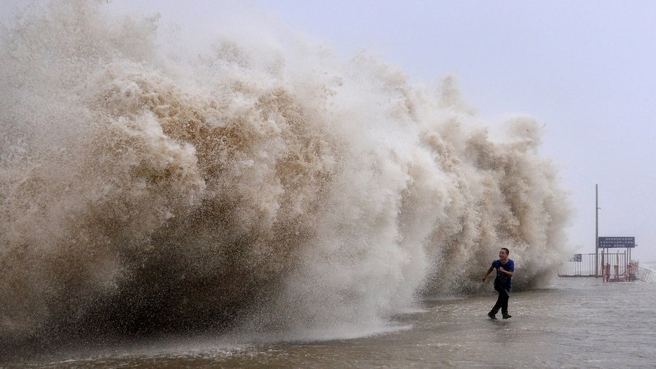 A man runs away from a huge wave pushed up by Typhoon Usagi in Shantou, south China's Guangdong province