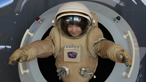 A woman tries out a space suit on display at the 64th International Astronautical Congress in Beijing