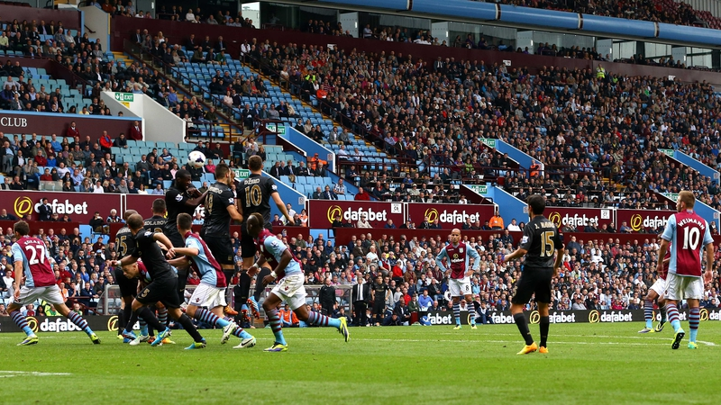 Leandro Bacuna of Aston Villa (right) curls the ball over the Manchester City wall