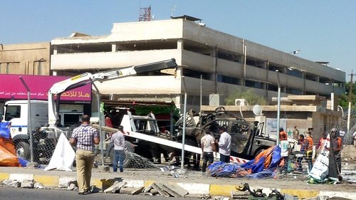 A destroyed vehicle is removed following a car bomb in a car park in Baghdad