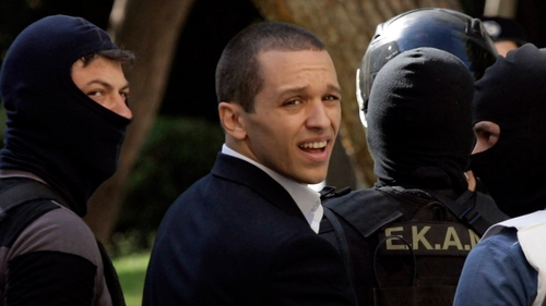 Golden Dawn spokesman Ilias Kasidiaris is escorted by anti-terror police into court