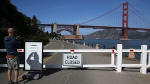 A visitor takes a picture of a sign announcing the closure of the Fort Point National Historic Site in San Francisco