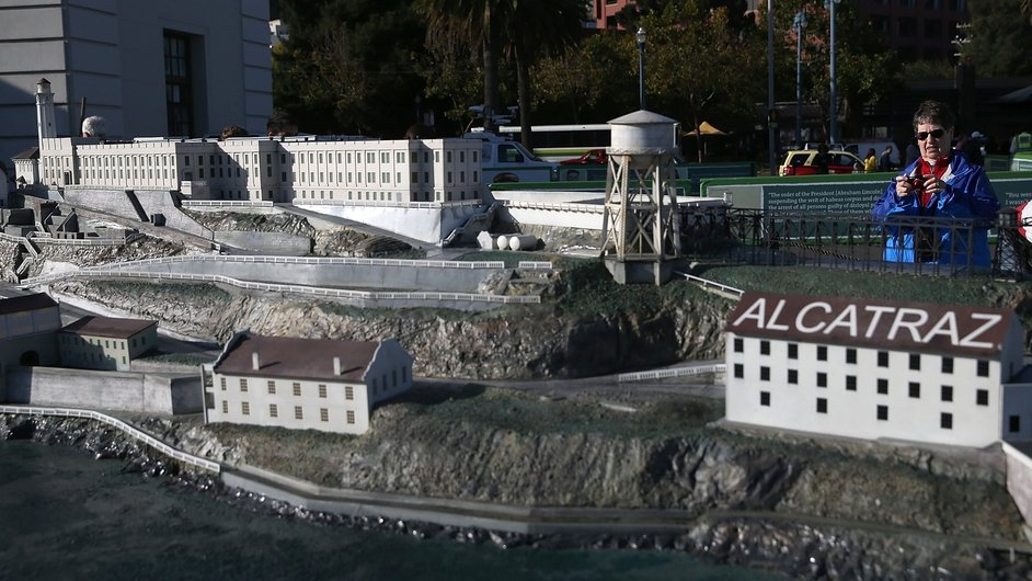 A woman takes a photograph of a scale model of Alcatraz, after the official tour was closed