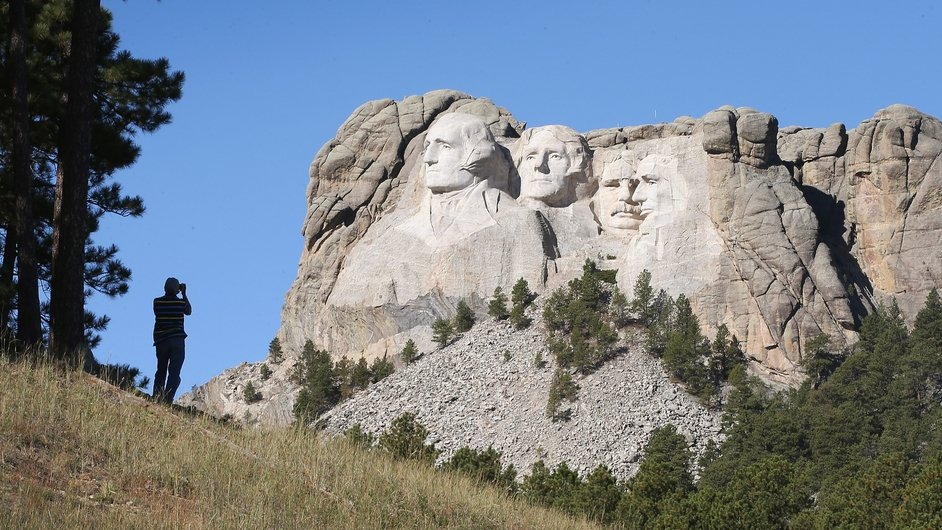 A tourist takes a picture of Mount Rushmore from a nearby field