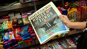 A woman buys a copy of the Daily News, depicting Republican House Speaker John Boehner