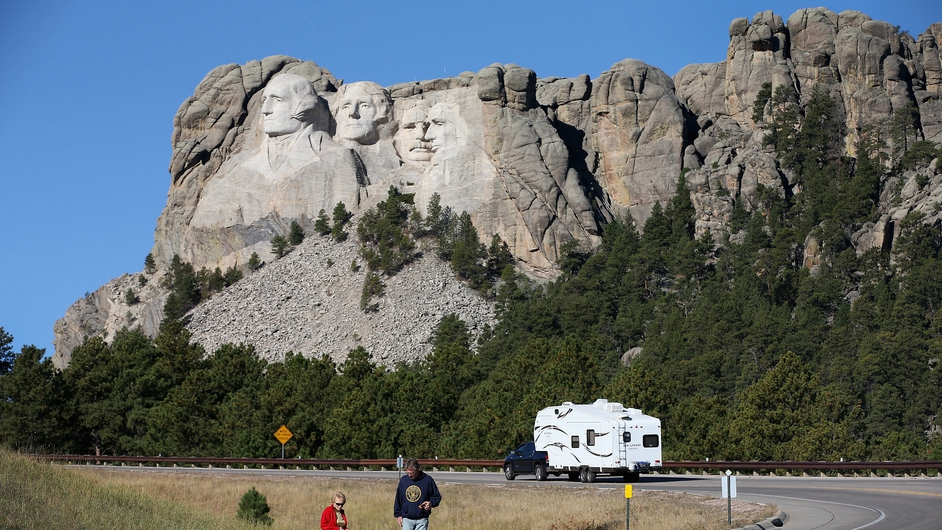 Tourists view Mount Rushmore from the road after the national park was shut
