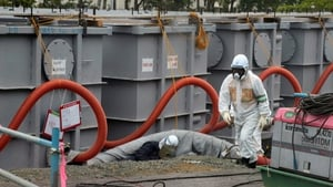 Workers examining waste water tanks at the Fukushima plant in June