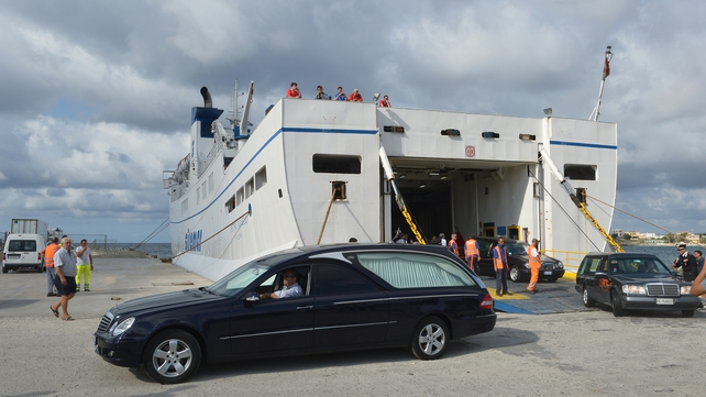 Funeral cars disembark from a ferry in the harbour of Lampedusa