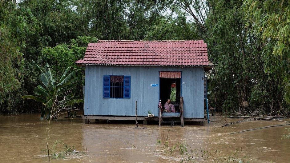 A woman sits in a flooded house in Tonle Bit commune in Cambodia, after the Mekong river broke its banks
