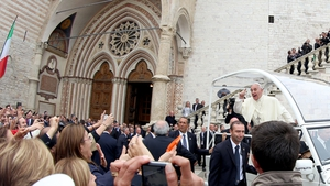 Pope Francis waves to the faithful as he leaves after the Mass at the Sacro Convento and Saint Francis Basilica