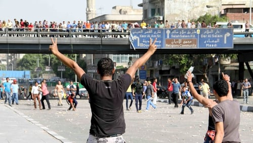Supporters (background) and opponents of ousted Egyptian president clashed in Cairo yesterday