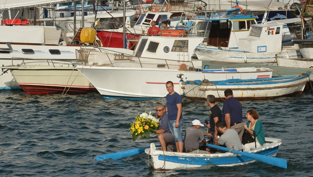 Fishermen prepare to put flowers in the Lampedusa harbour in Italy in memory of over 200 people who are thought to have died