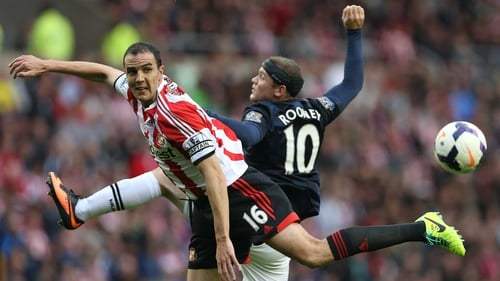 John O'Shea and Wayne Rooney vie for posession