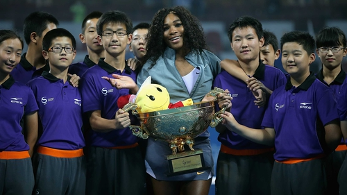 Serena Williams poses with the ball girls and boys after receiving her trophy