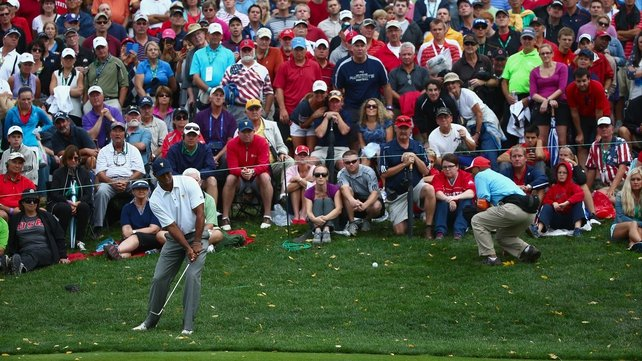 Tiger Woods hits a pitch shot on the 17th on the way to victory
