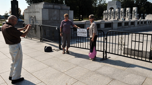 Tourists take photos behind a barricade preventing access to the World World II Memorial as the partial government shutdown continues