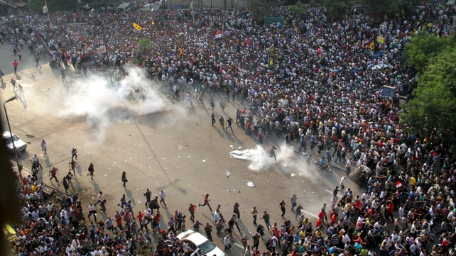 Protesters run for cover from tear gas during the clashes in Cairo
