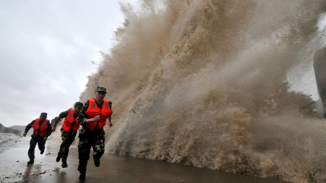 A huge wave hits as guards run along a dyke as Typhoon Fitow moves to make landfall