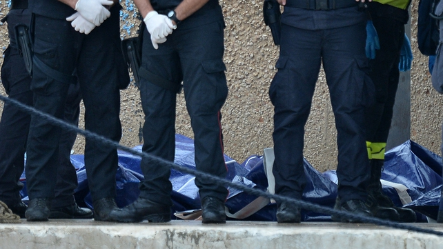 Police officers stand beside body bags containing the victims of the shipwreck in Lampedusa