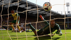 Anthony Pilkington of Norwich City turns to celebrate his goal as Petr Cech of Chelsea watches the ball go into the net