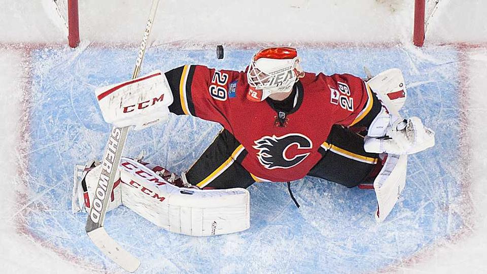Reto Berra #29 of the Calgary Flames watches the shot of Zbynek Michalek go over the line