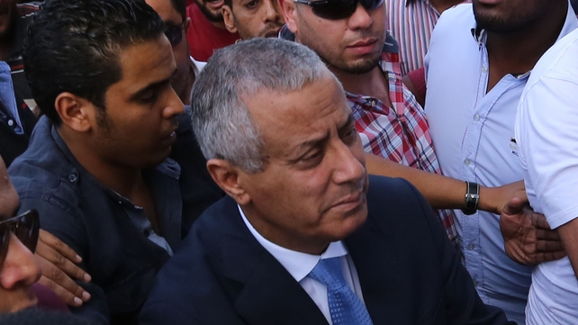 Libyan Prime Minister Ali Zeidan (C) arrives at the government headquarters in Tripoli after his release