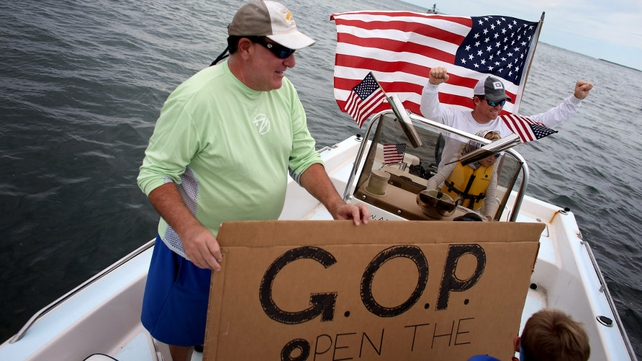 Fishing guide Captain Steve Friedman (R) and friend Sam Kaufman (L) participate in a floating protest asking the government to stop the shutdown and reopen the Florida everglades