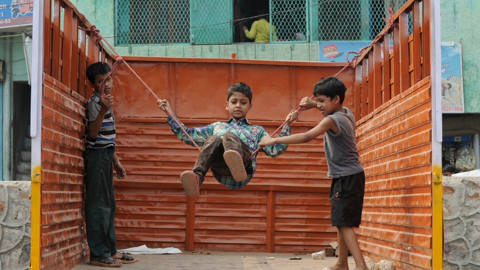 Indian children play on a swing strung up on the back of a truck in New Delhi