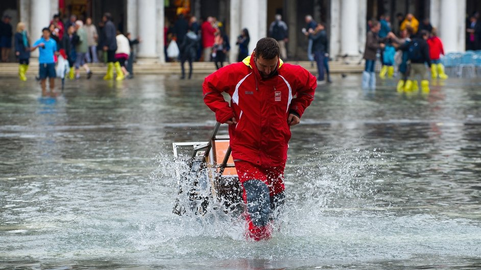 A delivery man walks with a trolley along Saint Mark's Square during the first 'Acqua Alta' of the season in Venice