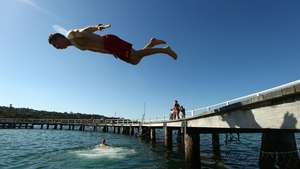 A man dives into the water at Balmoral Beach in Sydney as temperatures soared into the high 30s