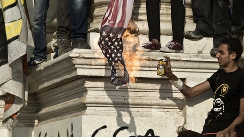 Mohammed Mursi supporters burn the American flag during a rally outside the presidential palace in Cairo
